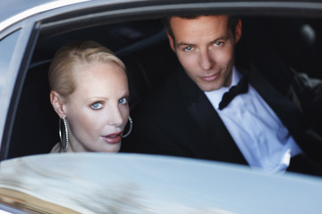 Celebrities sitting in backseat of car