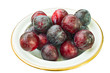 Dish of whole, ripe plums, with natural wax bloom