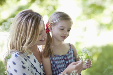 Mother and daughter examining flowers