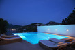 Pool with lounge chairs at night