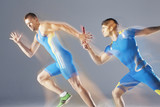 Blurred view of athletes passing baton