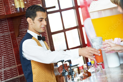 Cheerful arab barman at counter