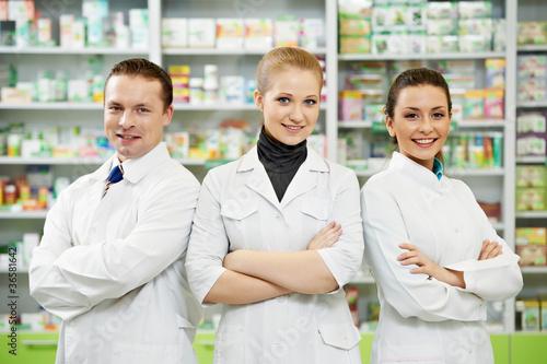 Leinwanddruck Bild Pharmacy chemist team women and man in drugstore