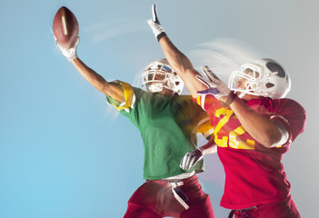 Blurred view of football players grabbing ball