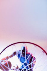 Basketball player viewed through hoop