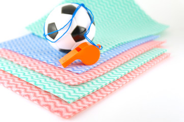 Football and whistle on the color napkins
