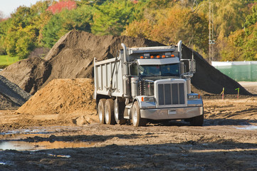 A dump truck about to unload a pile of dirt