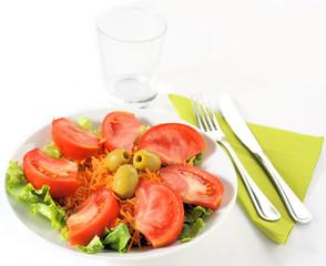 Piatto d'insalata con posate e bicchiere