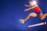 Athlete jumping over hurdles