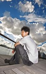 asian man sitting in park