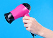 Pink hair dryer in the female hand