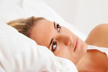 Frau liegt wach im Bett. Schlaflos