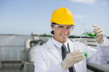 Scientist pouring liquid into beaker outdoors