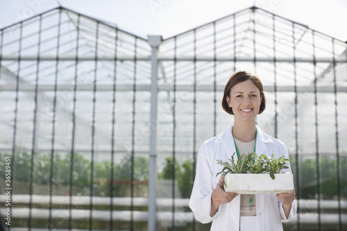 Scientist holding plants outside greenhouse