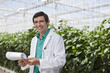 Scientist reading clipboard in greenhouse