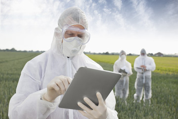Scientist in protective gear using tablet computer