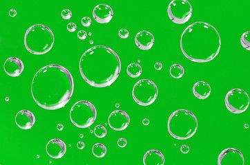 Water droplets on a green background.