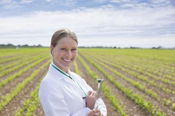 Scientist writing on clipboard in wheat field