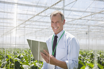 Businessman writing on clipboard in greenhouse