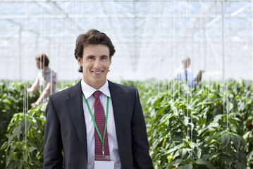 Businessman standing in greenhouse