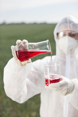 Scientist in protective gear pouring liquid into beaker