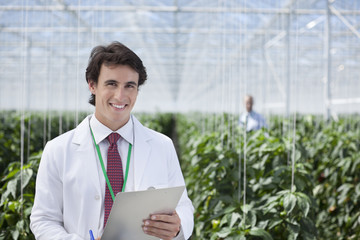 Scientist writing on clipboard in greenhouse
