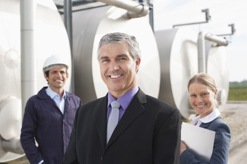Business people standing beside tanks outdoors