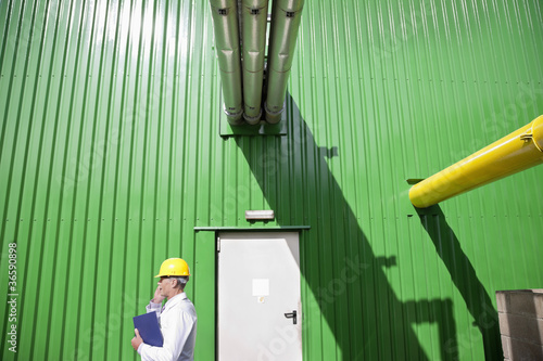 Technician talking on cell phone outside warehouse