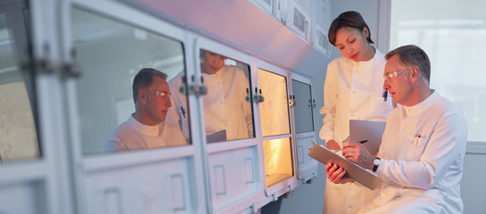 Scientists examining oven in lab