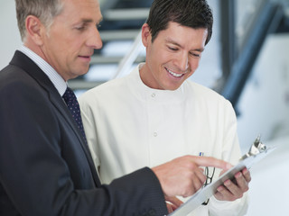 Businessman and scientist reading clipboard