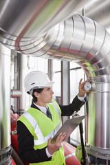 Businessman checking gauges on pipes in factory