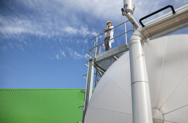 Scientist standing on walkway on tanks