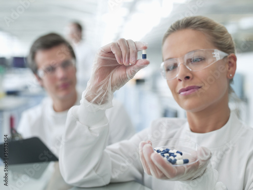 Scientists examining pills in lab