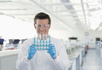 Scientist holding rack of test tubes in lab
