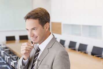Businessman speaking into microphone in conference room