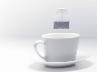 Tea bag hovering over coffee cup