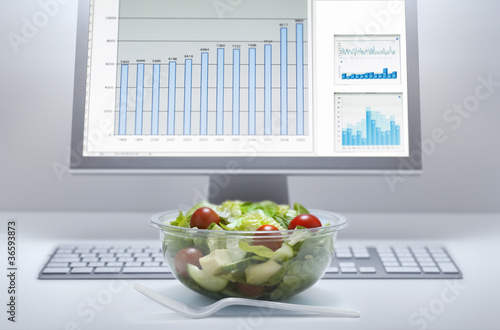 Bowl of salad at computer desk