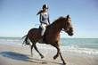 Girl riding horse on beach