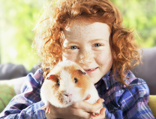 Girl holding pet hamster in living room