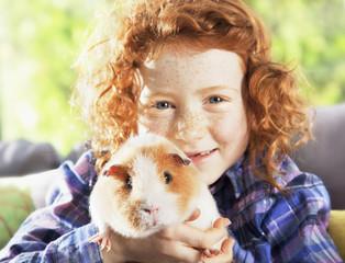 Girl holding pet hamster in living room