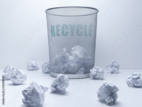 Crumpled balls of paper beside recycling bin