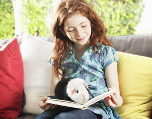 Girl reading with pet hamster