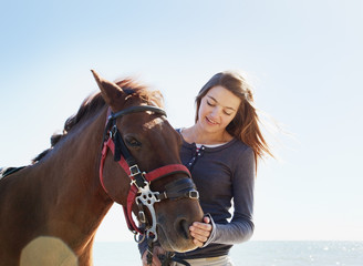 Girl petting horse on beach