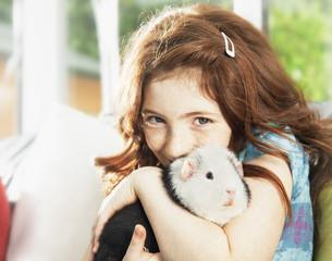 Girl hugging pet hamster