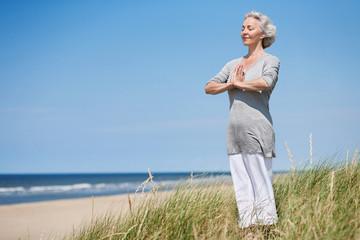 attraktive, grauhaarige Frau meditiert am Meer