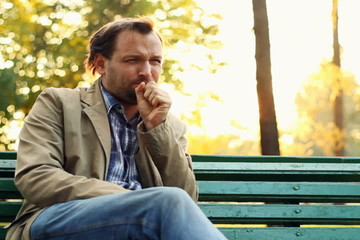 Sick man on park bench coughing