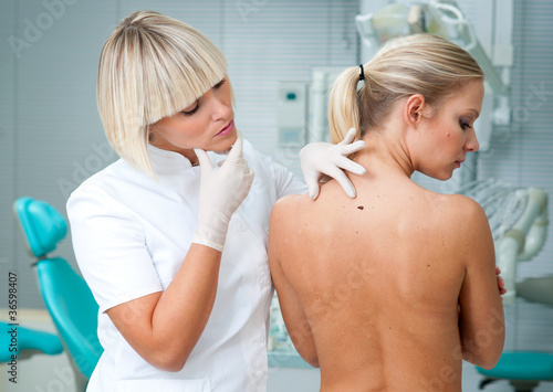 doctor inspecting woman patient skin