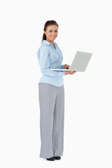 Smiling businesswoman with her laptop against a white background