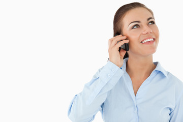 Smiling businesswoman looking upwards while on the phone