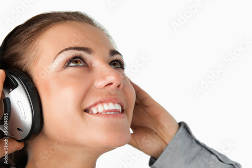 Close up of young businesswoman listening to music